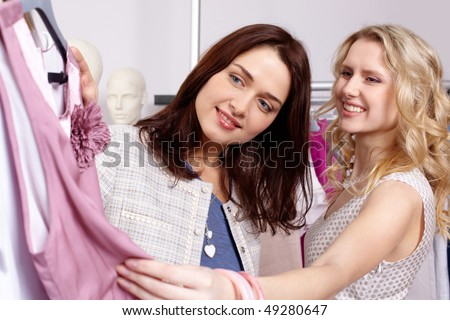 Image of pretty friends choosing tanktop in trade center - stock photo