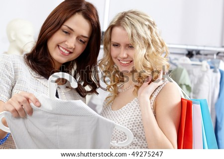 Image of pretty friends chosing clothes and talking in the department store