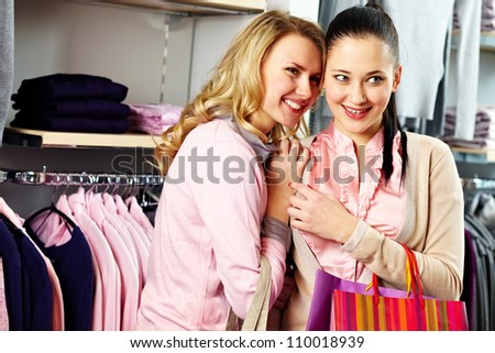 Image of pretty friends looking for new fashionable clothes in department store - stock photo