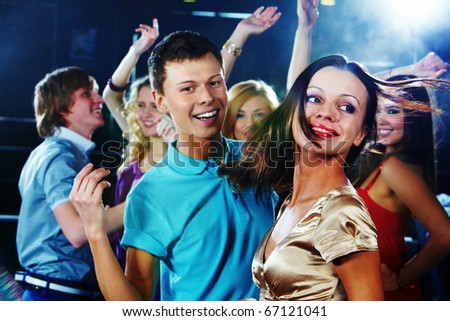 Image of pretty girl dancing on background of clubbing friends - stock photo