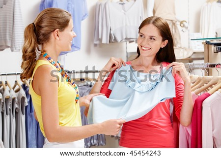 Image of pretty girl showing blue tanktop to her friend in the department store - stock photo