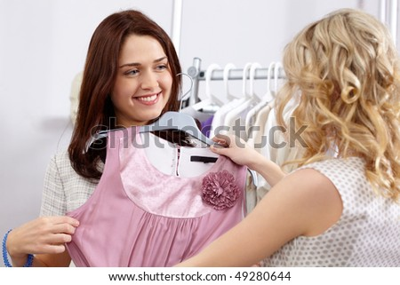 Image of pretty girl trying on tanktop with helpful assistant near by in the department store - stock photo