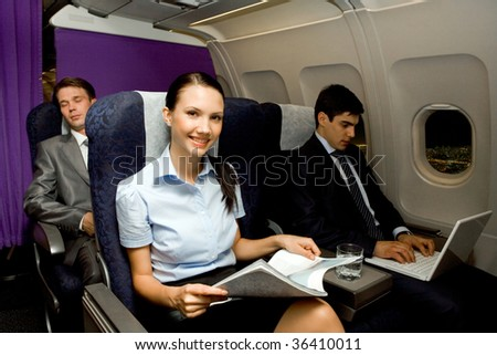 Image of pretty girl with magazine looking at camera while handsome man typing next to her - stock photo