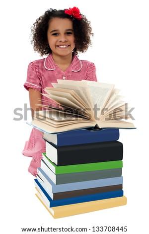Image of pretty schoolgirl reading textbook near pile of books. - stock photo