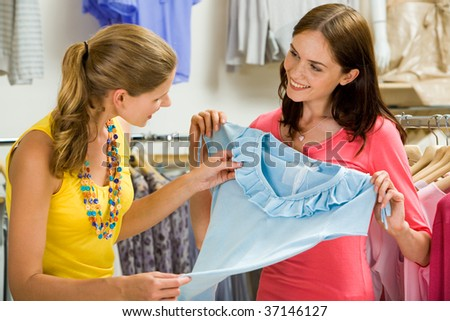 Image of pretty shop assistant showing blue tanktop to beautiful girl in the department store - stock photo