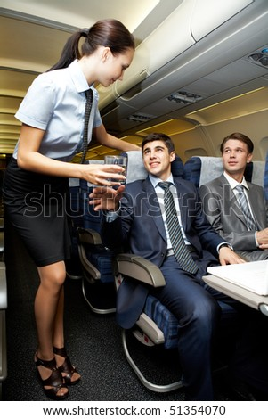 Image of pretty stewardess giving glass to businessman in airplane