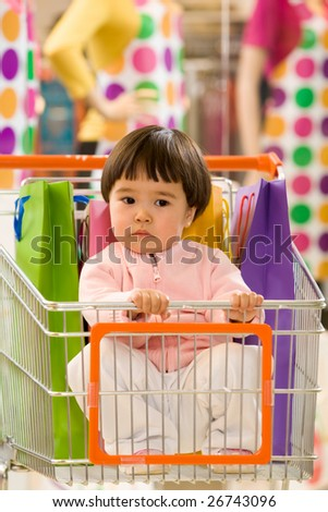 Image of pretty toddler in handcart in the shopping center looking aside - stock photo