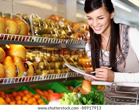 Image of pretty woman choosing products in supermarket with list of things to buy - stock photo