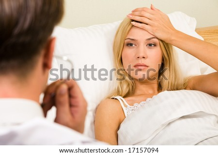 Image of pretty woman in bed touching her forehead and looking at doctor - stock photo