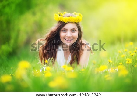 Image of pretty woman lying down on dandelions field, happy  cheerful girl resting on dandelions meadow, relaxation outdoor in springtime, vacation - stock photo