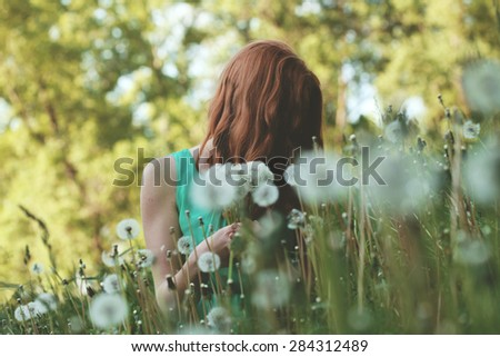 Image of pretty woman sitting on dandelions field, happy cheerful girl resting on dandelions meadow, relaxation outdoor in springtime, vacation - stock photo