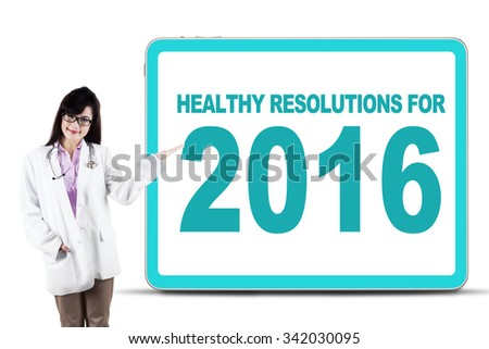 Image of pretty young doctor showing a billboard with healthy resolution for 2016 - stock photo