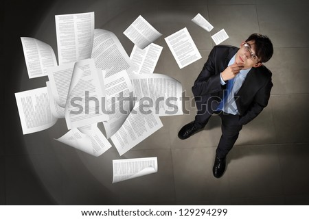 Image of printed materials flying in air top view against businessman background - stock photo