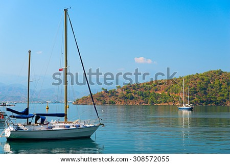 Image of pristine yachts and boats moored on the calm blue seas of the turkish riviera in mid summer - stock photo