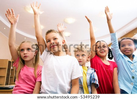 Image of pupils raising arms during the lesson - stock photo