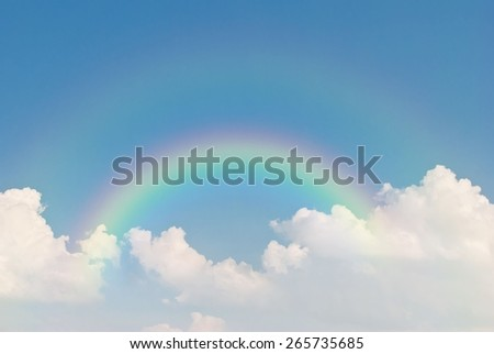 image of rainbow in blue sky and white clouds - stock photo
