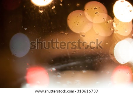 Image of raindrops on window at night in the city - stock photo