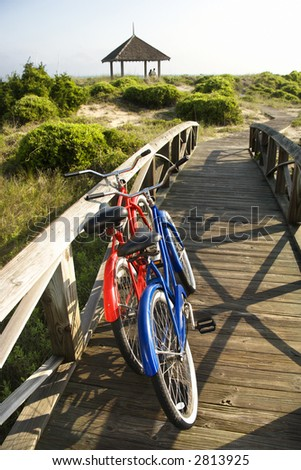 Image of red and blue bike leaning against railing of boardwalk. - stock photo