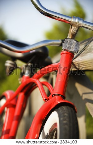 Image of red bike leaning against railing of boardwalk. - stock photo