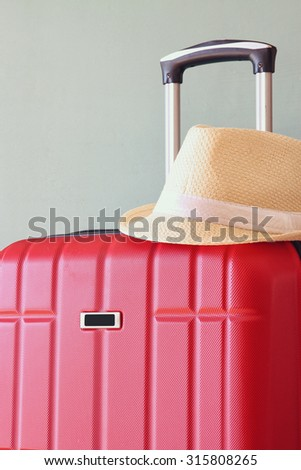 image of red elegant travel luggage and fedora hat in front of sea. travel and vacation concept  - stock photo