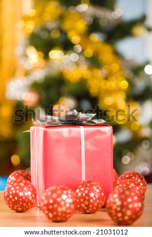 Image of red giftbox surrounded by several toy balls on glittering background