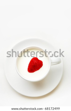 Image of red ripe strawberry heart inside cup of milk