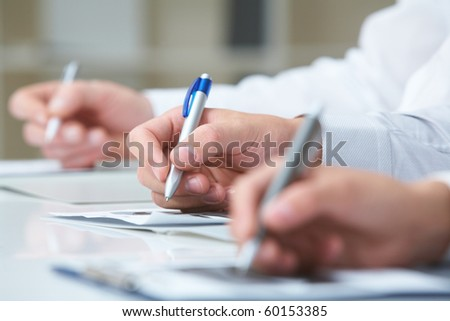 Image of row of people hands writing on papers at seminar - stock photo