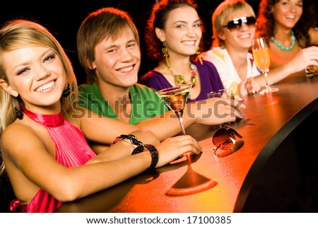 Image of row smiling teens with pretty girl in front in the nightclub