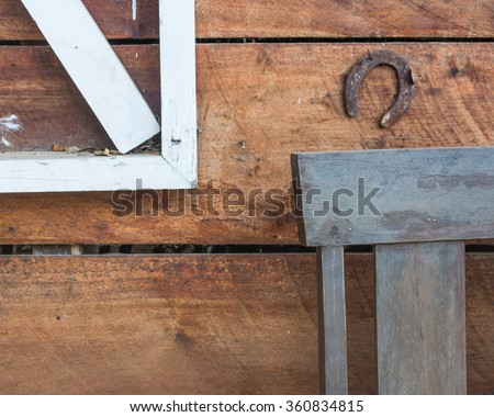 image of rusty horse shoe on wood wall for background usage. - stock photo