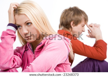Image of sad girl with confused guy at background after having an argument