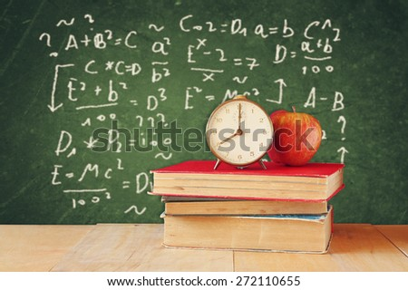 image of school books on wooden desk, apple and vintage clock over green background with formulas. education concept - stock photo