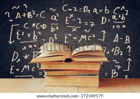 image of school books on wooden desk over black background with formulas. education concept - stock photo