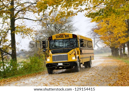 Image of school bus on the road with autumn trees and dried leaves - stock photo