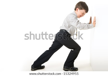 Image of schoolboy making great effort while setting against wall - stock photo