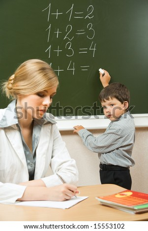 Image of schoolboy writing numbers on the blackboard and teacher sitting at the table  near by