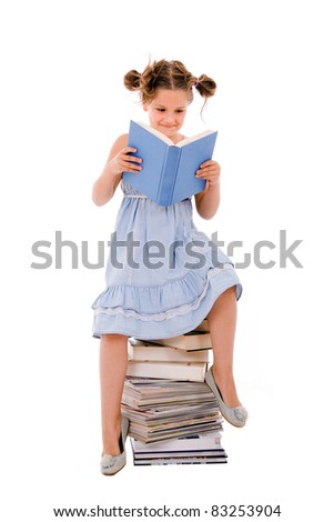 Image of schoolgirl sitting on the heap of books and reading one of them - stock photo