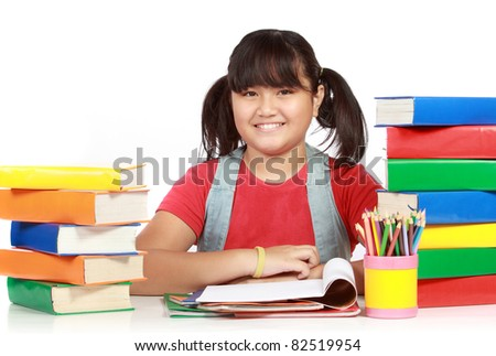 Image of schoolgirl smiling with the heap of books against white background - stock photo