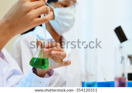 image of scientists experimenting and testing chemicals in laboratory  - stock photo