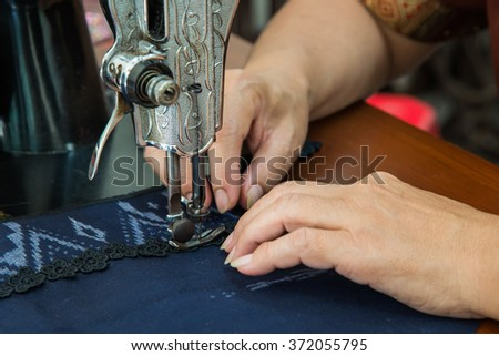 Image of seamstress working on sewing machine - stock photo