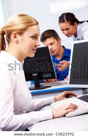 Image of secretary typing on the background of working colleagues