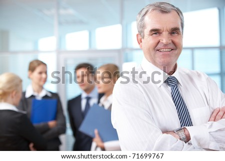 Image of senior leader smiling at camera in working environment - stock photo