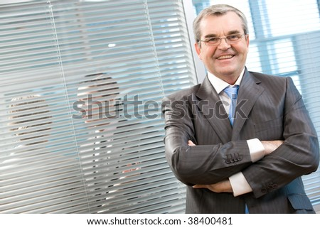 Image of senior leader smiling at camera on background of venetian blind - stock photo