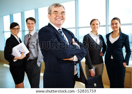 Image of senior leader smiling at camera with young business partners behind - stock photo
