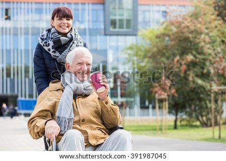 Image of senior man with walking problem and his carer - stock photo