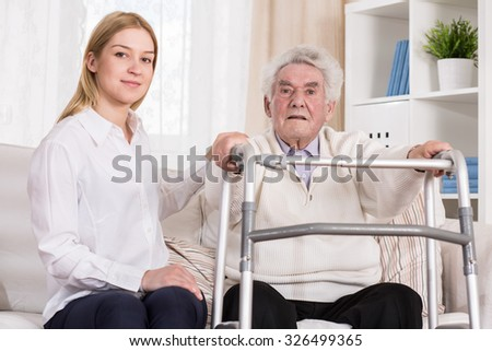 Image of senior man with walking zimmer and his carer - stock photo