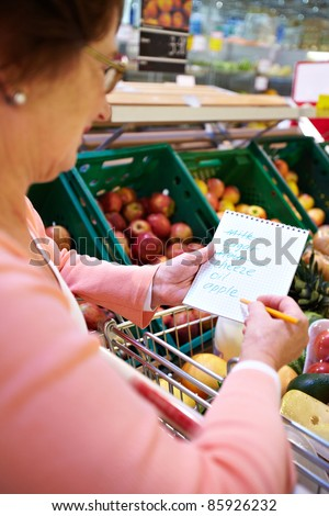 Image of senior woman looking at product list with goods in cart near by - stock photo