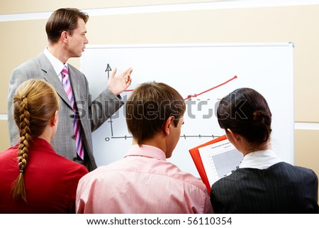 Image of serious businessman pointing at whiteboard with three partners listening to him