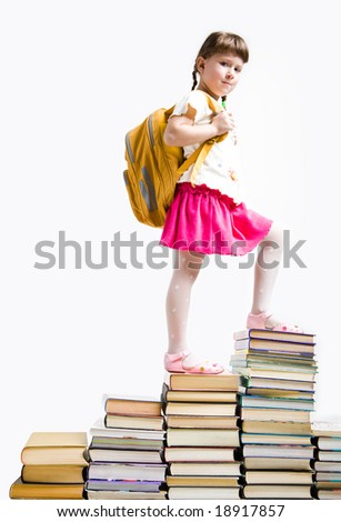 Image of serious schoolgirl standing on book stairs and looking at camera - stock photo