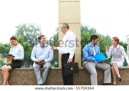 Image of several business partners interacting and working outside with papers - stock photo