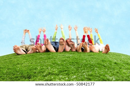 Image of several children lying on the grass and stretching their hands to the sun - stock photo